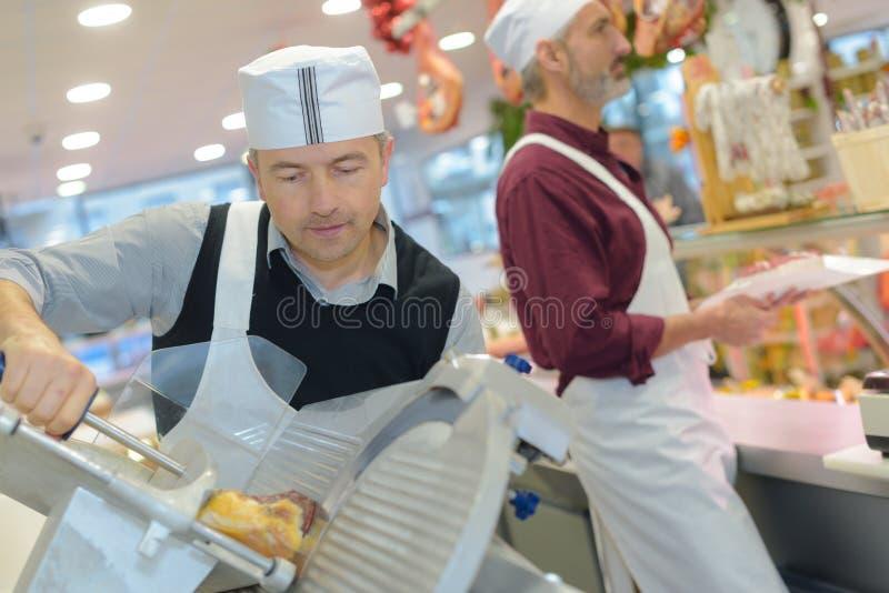 Man som skivar kött på delikatessaffärräknaren royaltyfri foto