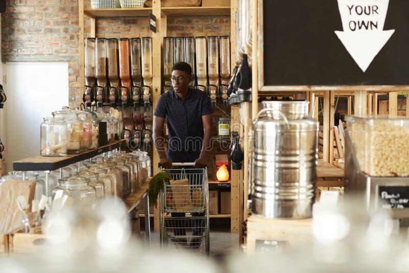 Man som skjuter shoppa spårvagnen till och med avsnitt för torkat gods av den hållbara plast- fria livsmedelsbutiken arkivbild