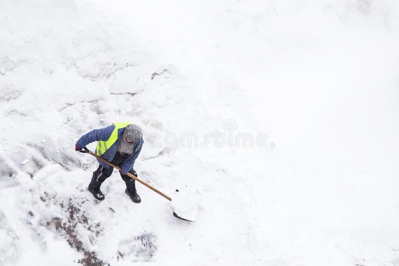 Man som skyfflar snö, kopieringsutrymme Bästa sikt av snörensning royaltyfri fotografi