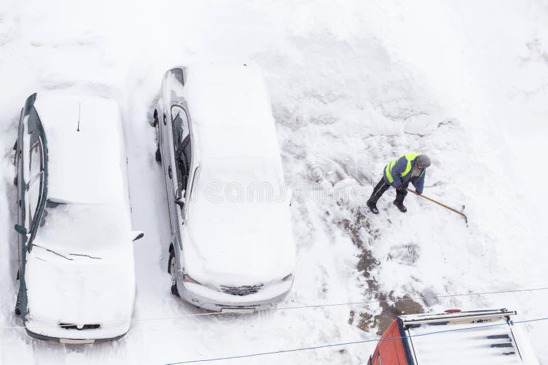 Man som skyfflar snö nära bilar på parkering Bästa sikt av snörensning arkivfoton