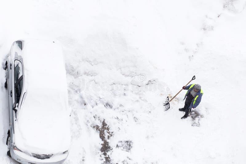 Man som skyfflar snö nära bilar på vägen, parkering arkivfoto