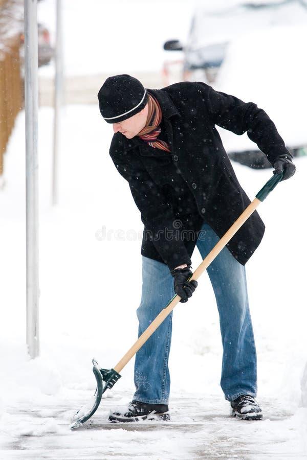 Man som skyfflar snow