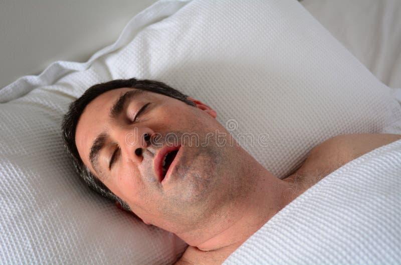 Man som snarkar i säng arkivfoton