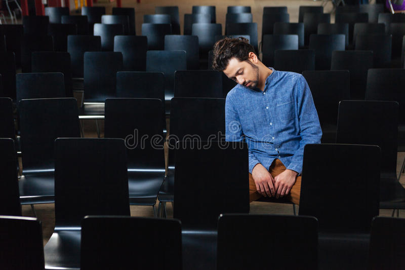 Man som sover i konferenskorridor arkivbild