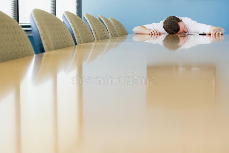 Man som sover på konferenstabellen arkivfoto