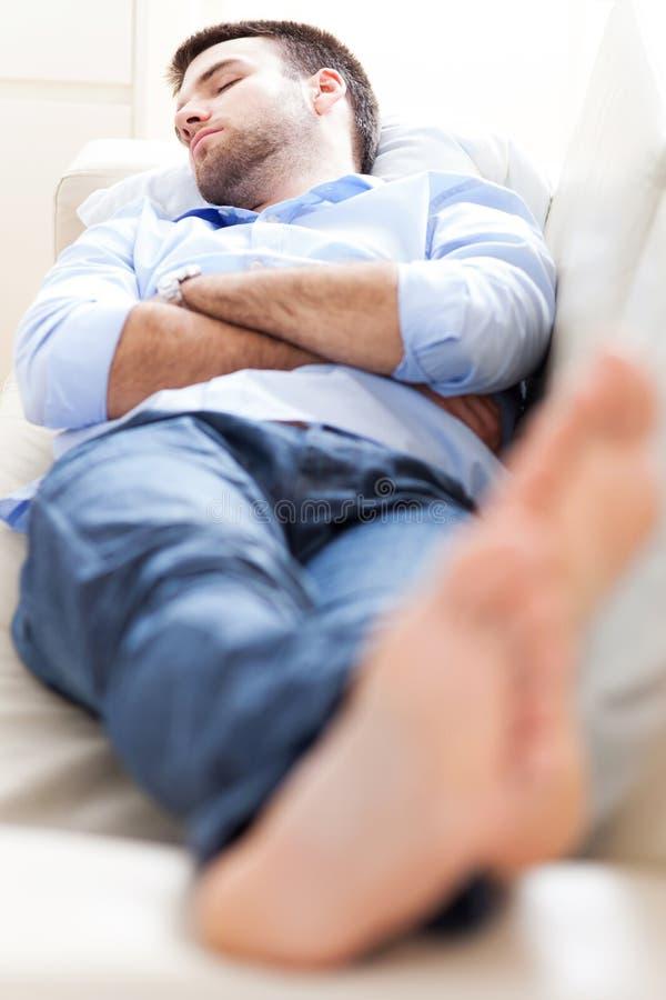 Man som sover på soffan royaltyfri foto