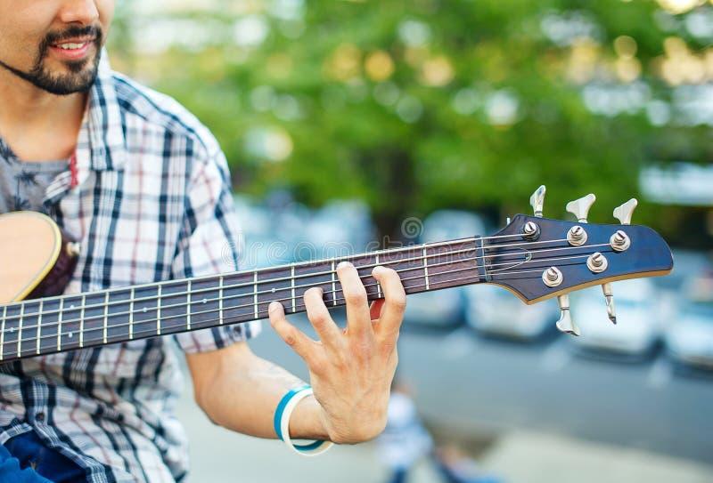 Man som spelar bas- närbild för akustisk gitarr arkivbild