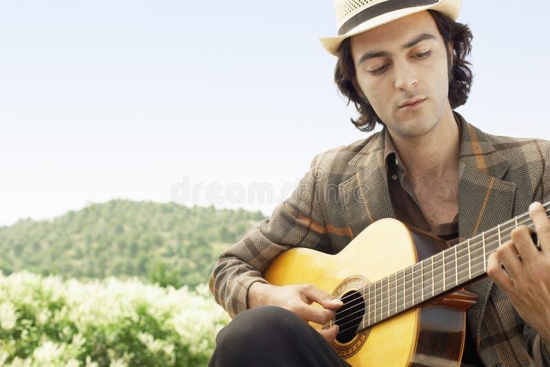 Man som spelar den akustiska gitarren arkivfoton