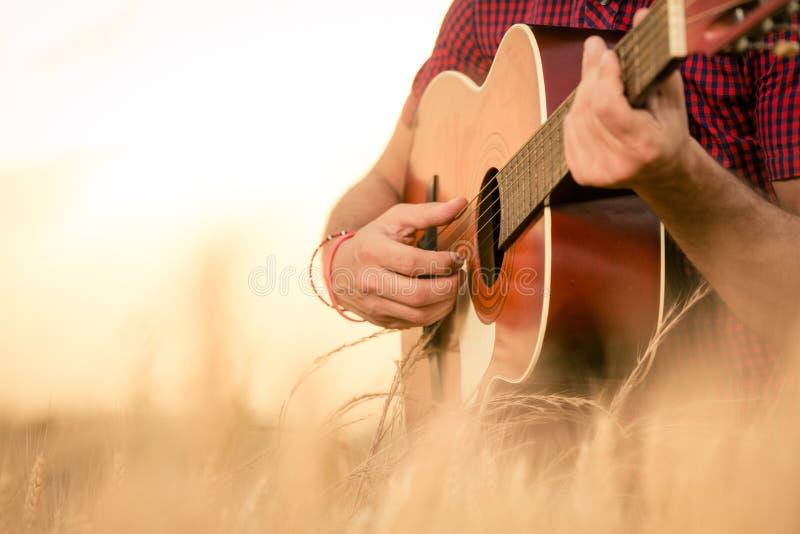 Man som spelar den akustiska gitarren på fältet royaltyfria bilder