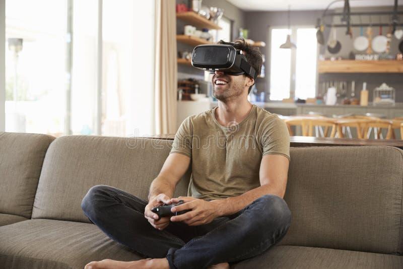 Man som spelar den bärande virtuell verklighethörlurar med mikrofon för dataspel royaltyfri foto
