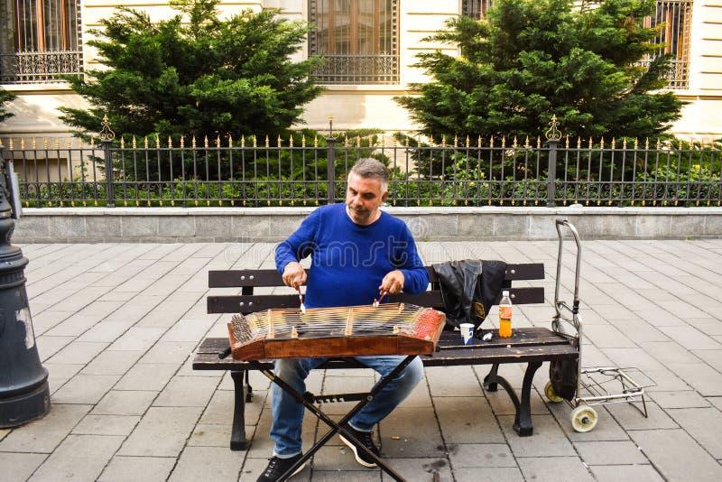 Man som spelar den traditionella bultade cymbalen med klubbor Gatakonstnären spelar sånger på Bucharest'sens gator i centrum royaltyfria foton