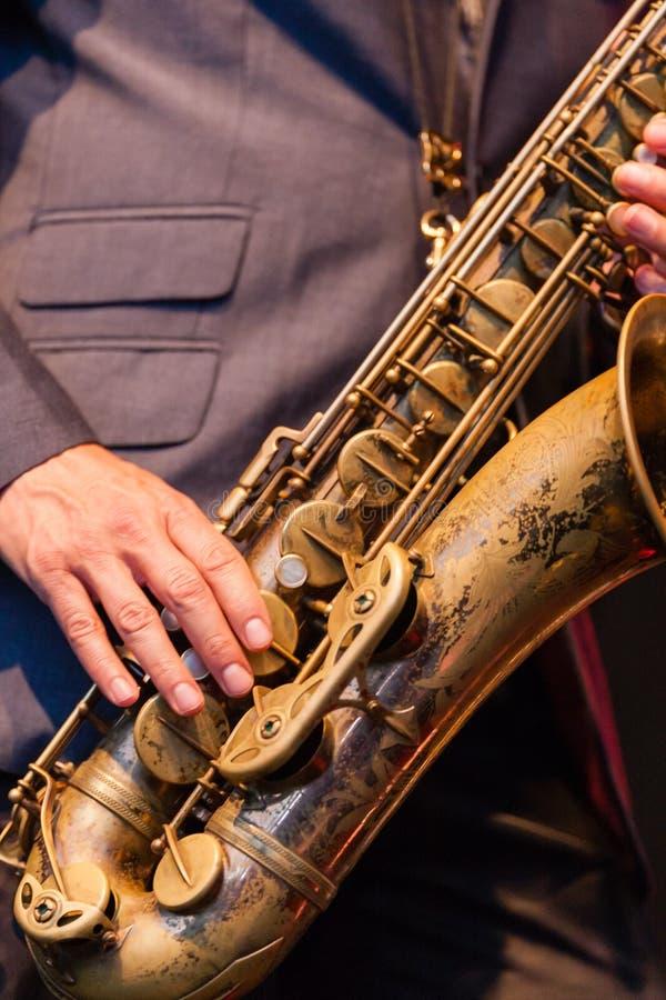 Man som spelar en tenorsaxofon fotografering för bildbyråer