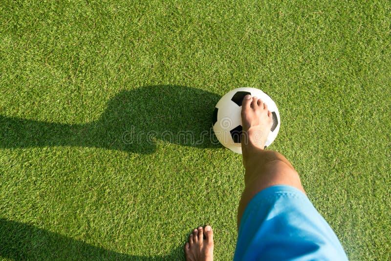 Man som spelar fotboll- eller fotbollbollen med kal fot arkivbild
