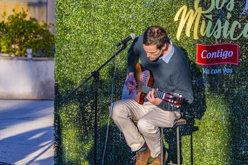Man som spelar gitarren på den ganska händelsen för gata, Montevideo, Uruguay arkivfoto