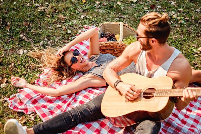Man som spelar gitarren till hans flicka arkivbilder