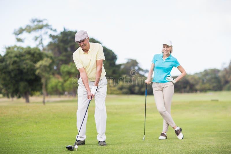 Man som spelar golf, medan stå vid kvinnan royaltyfria bilder
