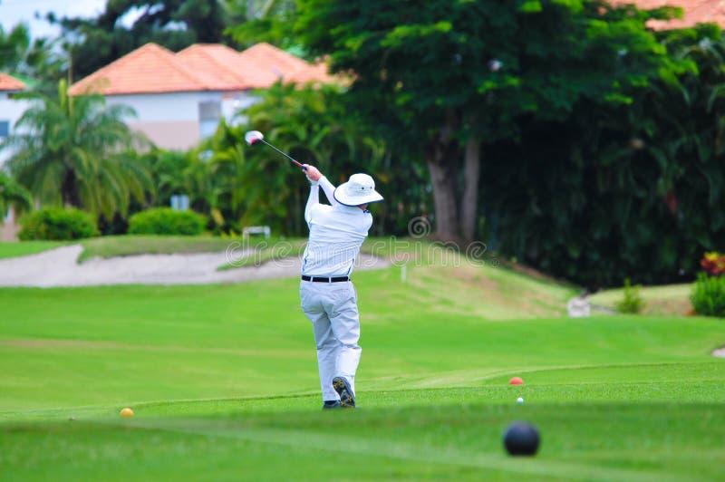 Man som spelar golf på en golfbana arkivbilder