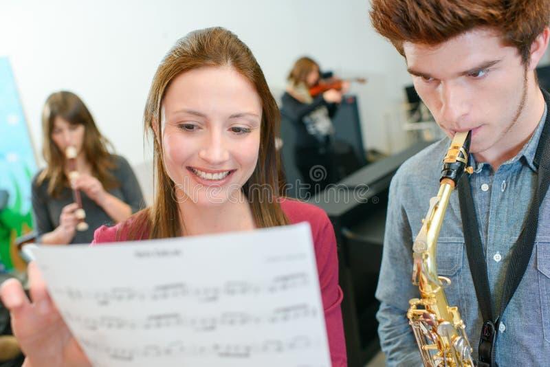 Man som spelar hållande musik för saxofonkvinna arkivbilder