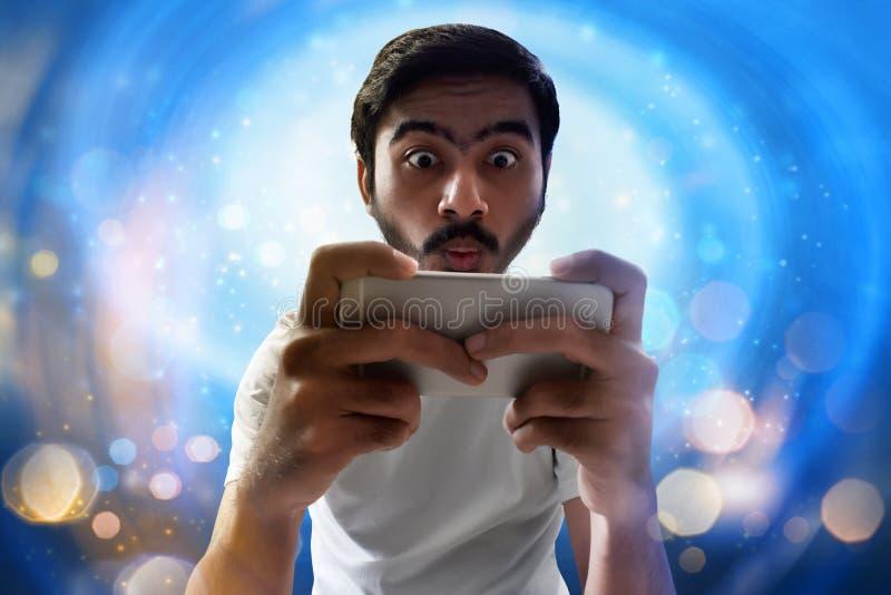 Man som spelar mobillekar på bokehbakgrund royaltyfri foto