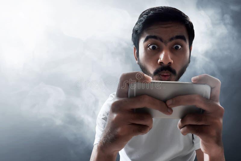 Man som spelar mobillekar på rökbakgrund fotografering för bildbyråer