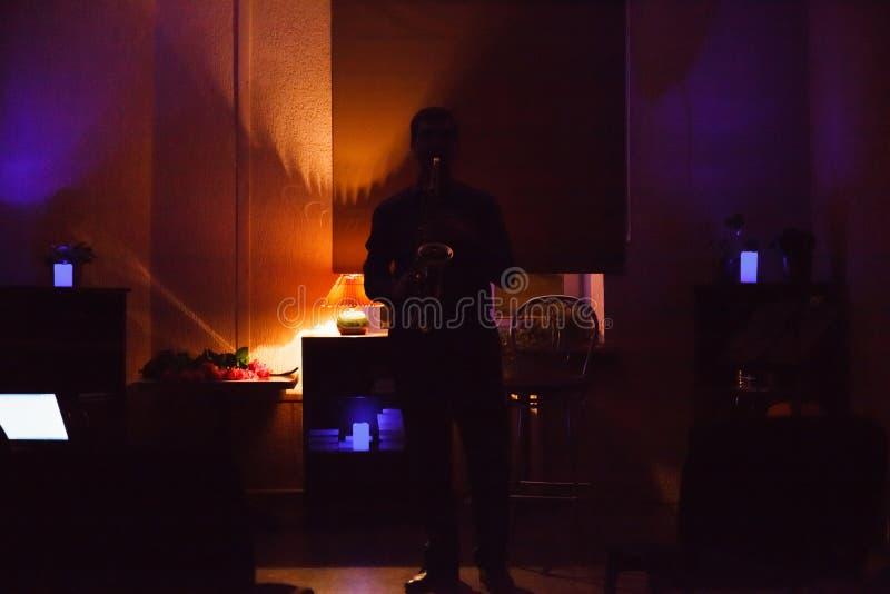 Man som spelar på saxofonen i mörkt rum royaltyfri bild