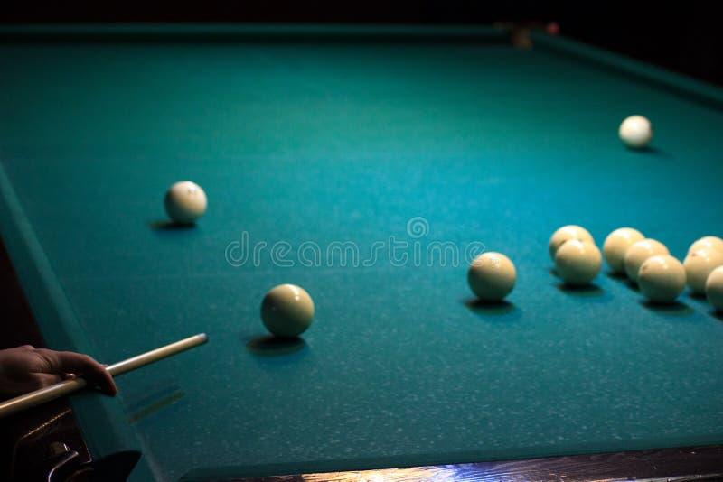 Man som spelar rysk biljard handen rymmer stickrepliken och har bollen på den gröna bakgrunden av tabellen sätt bollen in fotografering för bildbyråer