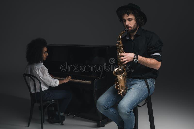 man som spelar saxofonen medan hans partner som spelar det gjorda suddig pianot fotografering för bildbyråer