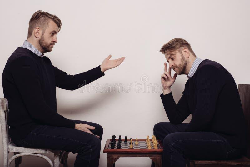 Man som spelar schack mot honom royaltyfria foton