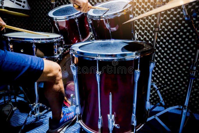 Man som spelar valsuppsättningen med trätrumpinnar och bastrumman med foten i musikrum fotografering för bildbyråer