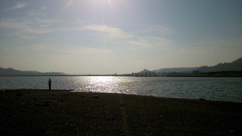 Man som ställa i skuggan av den jätte- sjön fotografering för bildbyråer