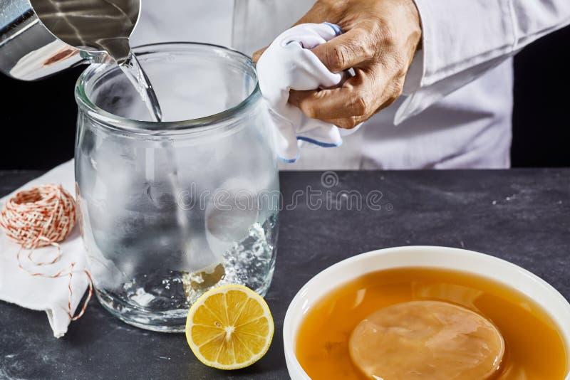 Man som steriliserar en glass krus med kokande vatten fotografering för bildbyråer
