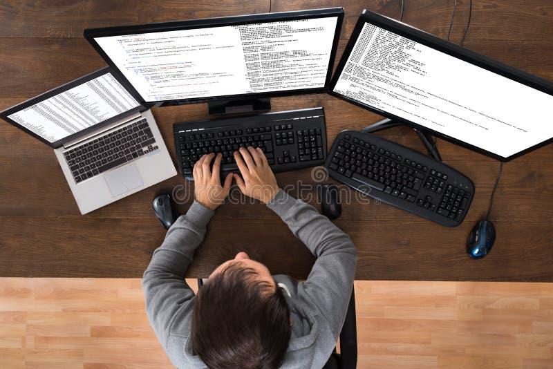 Man som stjäler data från datorer och bärbara datorn royaltyfri foto