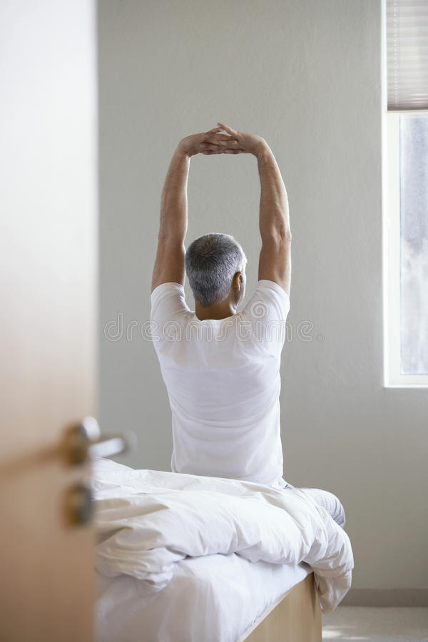 Man som sträcker händer, medan sitta på kanten av säng arkivfoto