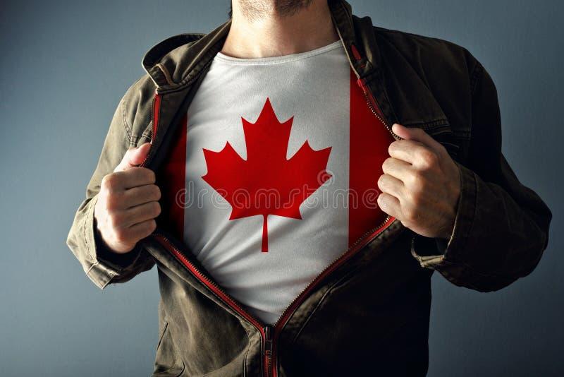 Man som sträcker omslaget för att avslöja skjortan med den Kanada flaggan fotografering för bildbyråer