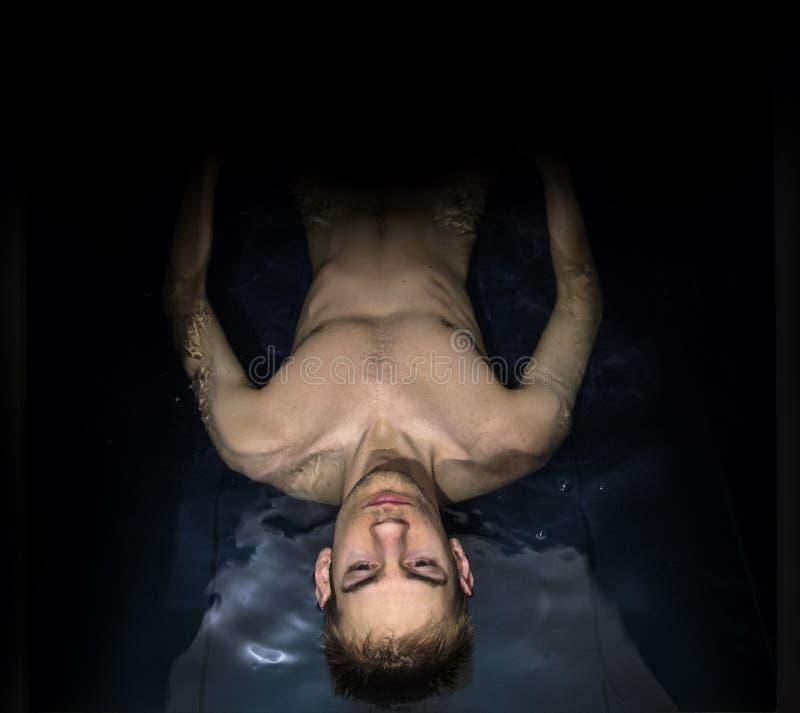 Man som svävar i en sensorisk förlustisoleringsbehållare royaltyfri fotografi