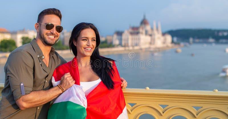 Man som täcker den lyckliga kvinnan med den ungerska flaggan på Budapest på Marg royaltyfri bild