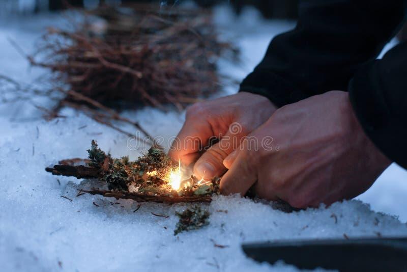 Man som tänder en brand i en mörk vinterskog royaltyfria bilder