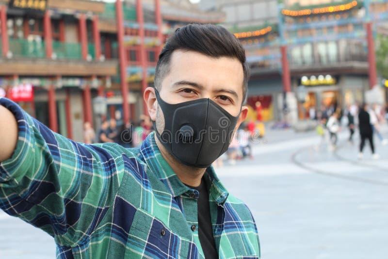 Man som tack vare bär en föroreningvarning för maskering fotografering för bildbyråer