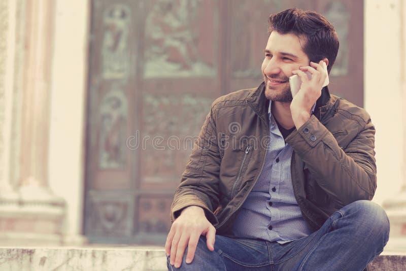 Man som talar på en telefon Tillfällig yrkesmässig användande smartphone som ler utanför gammal byggnad fotografering för bildbyråer