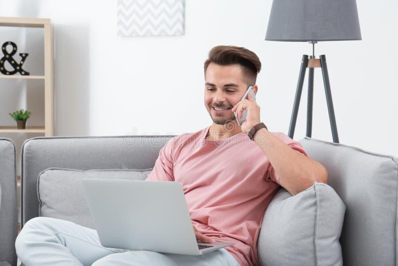 Man som talar vid mobiltelefonen, medan genom att använda bärbara datorn royaltyfri fotografi