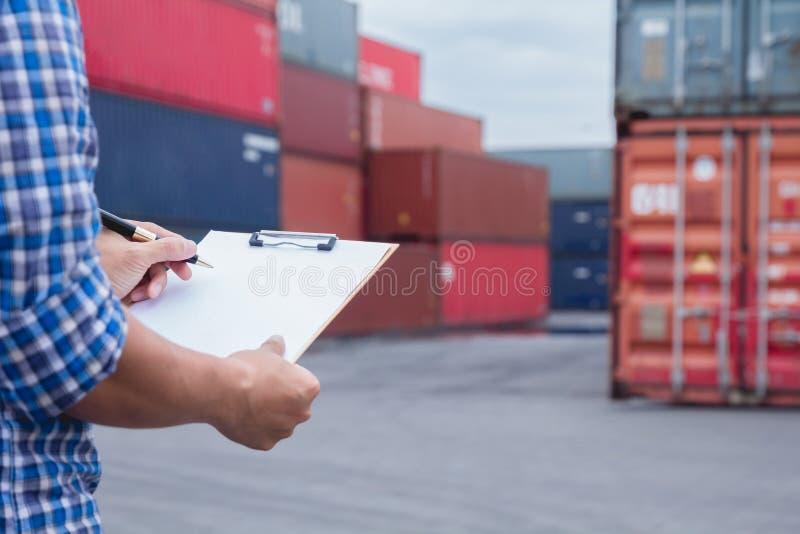 Man som tar anmärkningen som kontrollerar lastsändnings på behållaregårdområde royaltyfria bilder