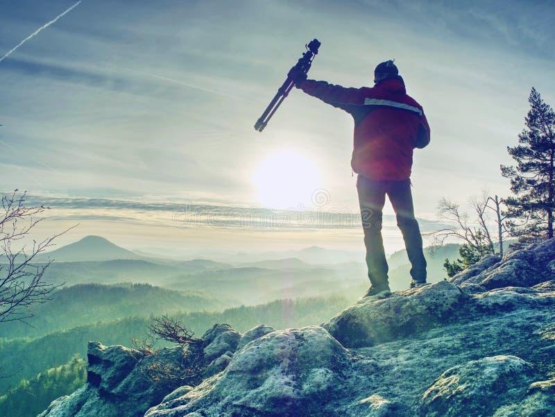 Man som tar bilden av landskapet när soluppgång på bergmaximumet arkivfoto