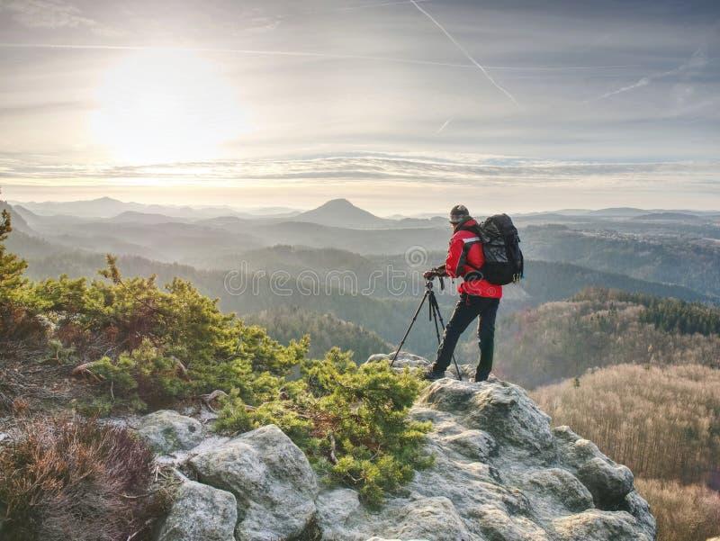 Man som tar bilden av landskapet när soluppgång på bergmaximumet royaltyfri bild