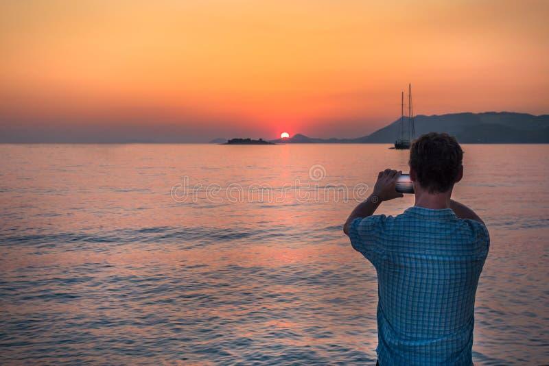 Download Man Som Tar Bilden Med Mobiltelefonen På Solnedgången, Kroatien Fotografering för Bildbyråer - Bild: 69425417
