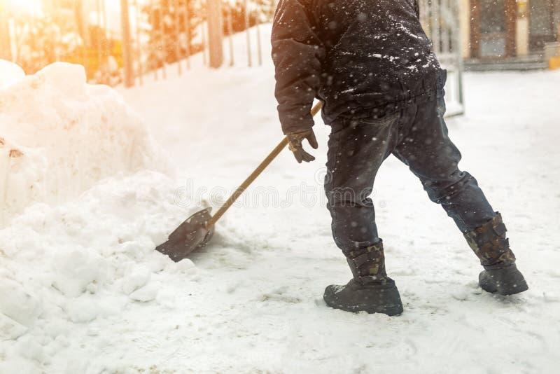 Man som tar bort snö från trottoaren efter tungt snöfall Snöstorm- och häftig snöstormefterdyning i vinter Hal promenadseger arkivfoton