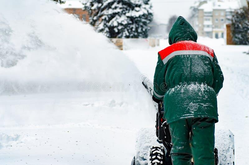 Man som tar bort snow med en snowblåsare fotografering för bildbyråer