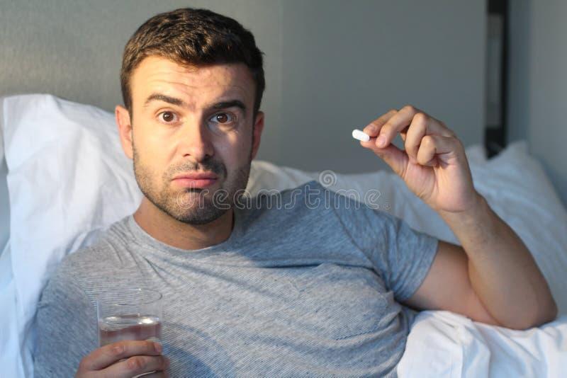 Man som tar en preventivpiller i säng royaltyfri foto