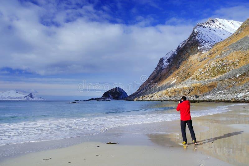 Man som tar foto på den Haukland stranden, Lofoten skärgård, i vinter royaltyfri bild