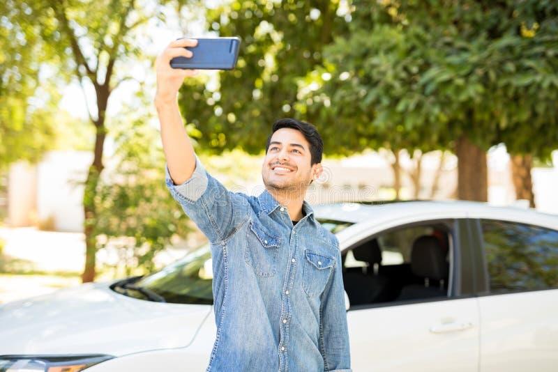 Man som tar selfie med hans nya bil arkivbilder