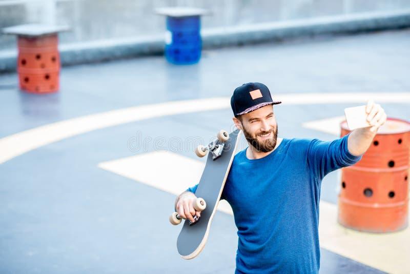 Man som tar selfiefotoet med skateboarden arkivbilder